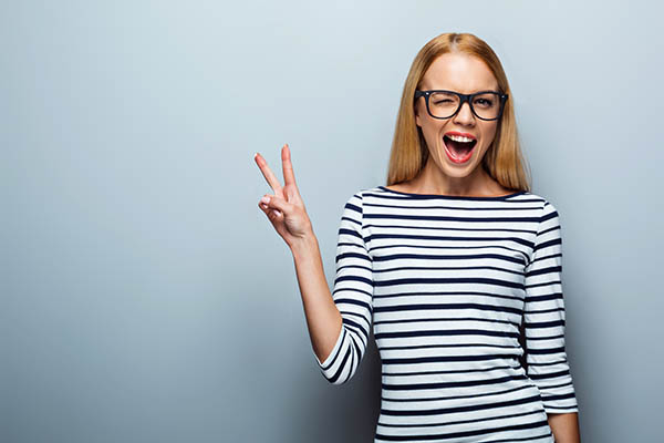 Portrait of beautiful caucasian blonde woman standing on grey background. Young woman with glasses cheerfully smiling and showing victory sign